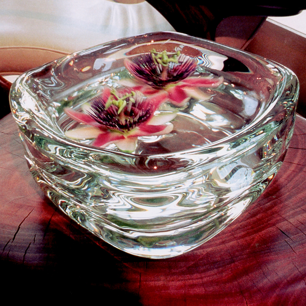 thick clear glass bowl filled with flowers, designer glass vase by siemon and salazar